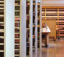 Student studying in the library stacks